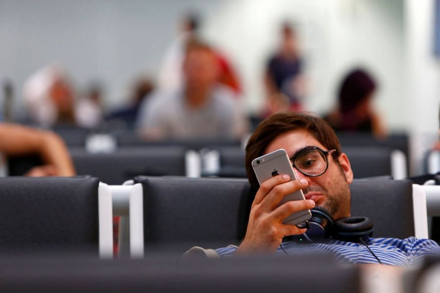 A man uses his iPhone while waiting for a plane at Munich airport in Germany.