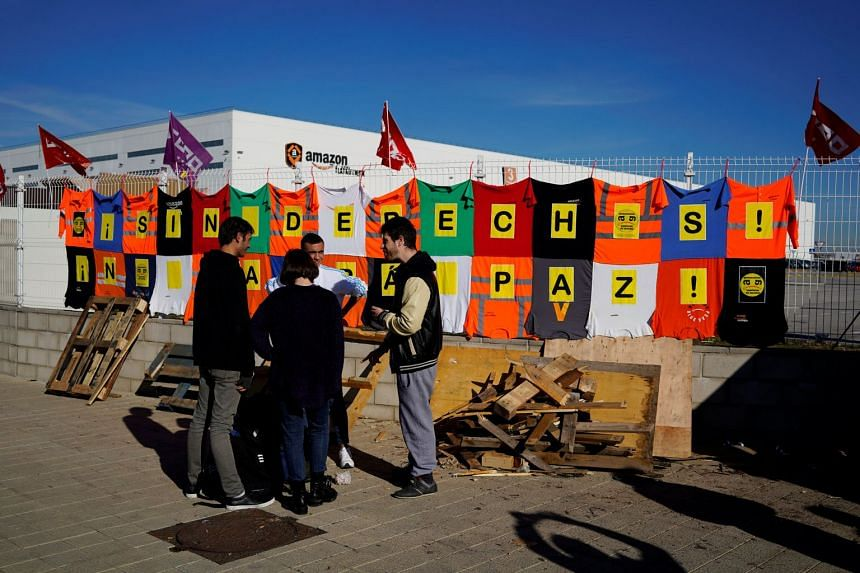 Workers stand outside the Amazon fulfilment centre in San Fernando de Henares near Madrid, Spain.