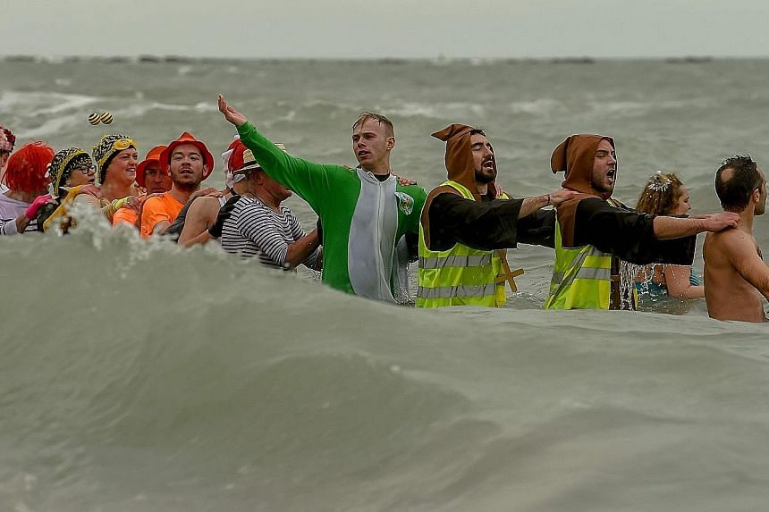 """Swimmers running into the North Sea for the New Year's Day swimming event on Norderney Island off Germany, while revellers (below) join the traditional """"bain des givres"""" at Malo-les-Bains beach in France."""