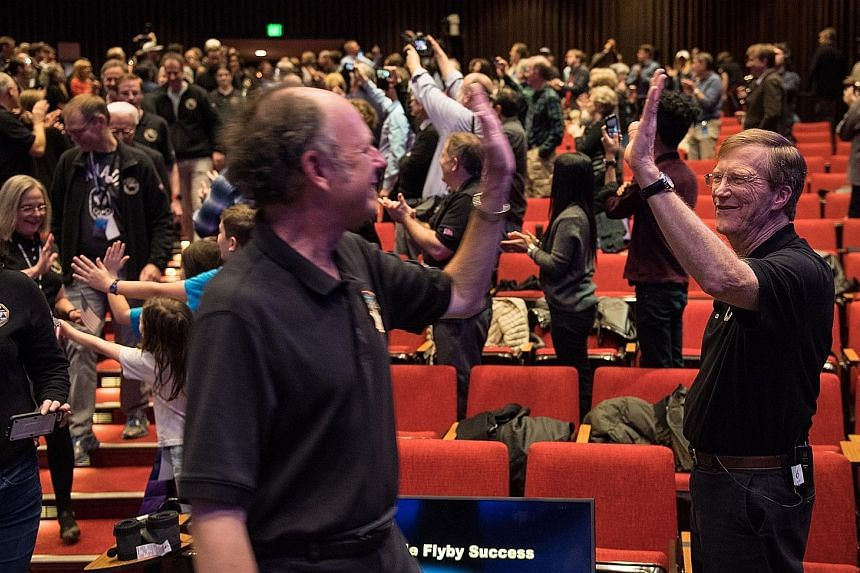New Horizons project scientist Hal Weaver (right) of the Johns Hopkins Applied Physics Laboratory is seen in a Nasa photo high-fiving a team member on New Year's Day after receiving confirmation that New Horizons has completed a fly-by of Ultima Thul