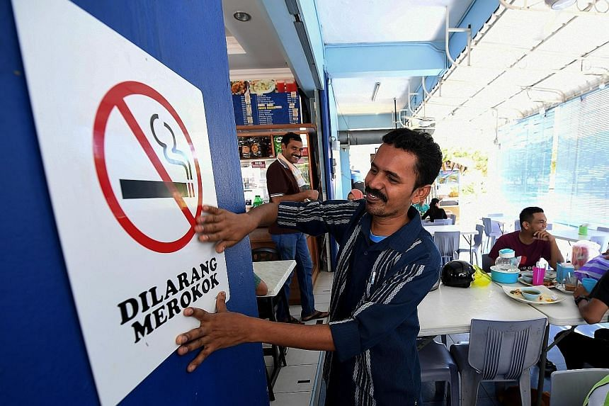 An employee of an eatery in Sandakan, Sarawak, putting up a no-smoking sign on Tuesday, the day the ban kicked in.