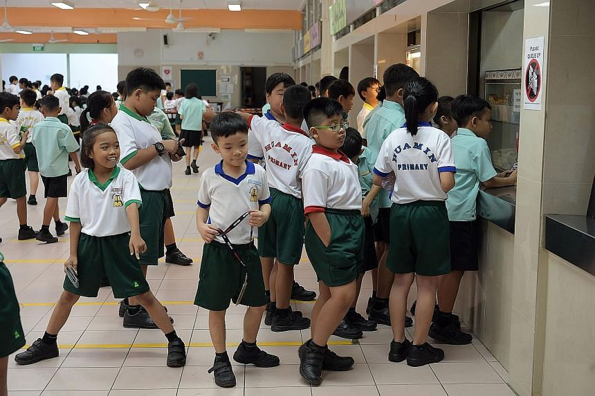 Education Minister Ong Ye Kung chatting with Primary 1 pupils on their first day of school at Huamin Primary yesterday. At the school, he launched mobile app Parents Gateway, which aims to improve communication between parents and schools at the prim