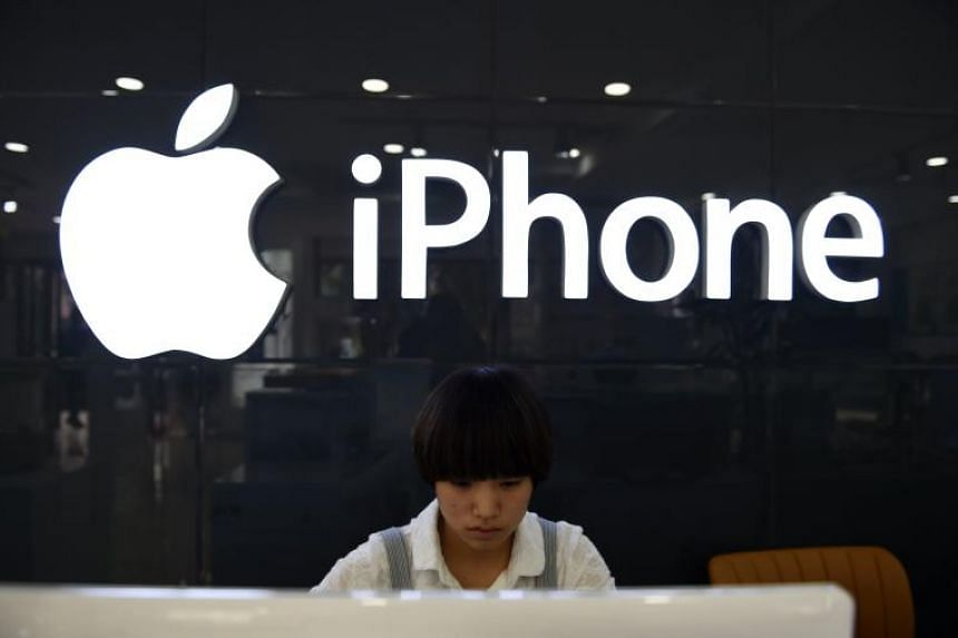 A shop assistant works behind a computer at a store selling Apple products in Beijing. Apple's revenue cut raises questions about whether Apple, the face of American business in many parts of the world, is being punished by Chinese officials or consu