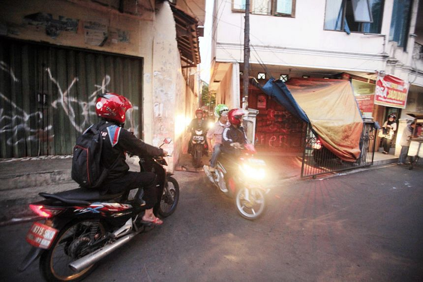 A motorcyclist is seen waiting for several riders to pass through a narrow alley in Kemanggisan, Palmerah, West Jakarta.