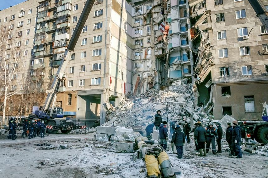 Russian Emergency Situations Ministry members work at the site of a partially collapsed apartment block in Magnitogorsk, Russia, on Jan 1, 2019.