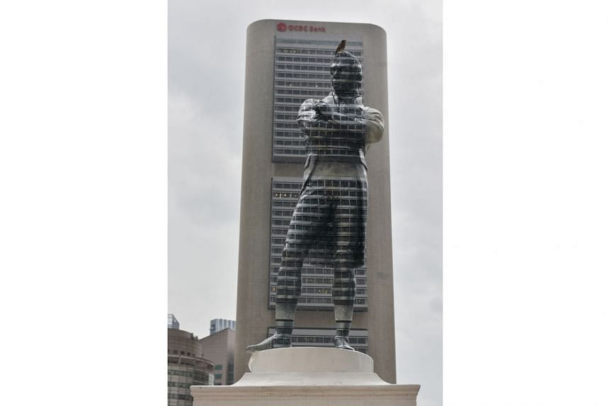 The statue of Sir Stamford Raffles is painted to blend into the buildings behind it. A sign near the statue indicates the optimum angle to take a photo of the statue such that it blends in with the background.