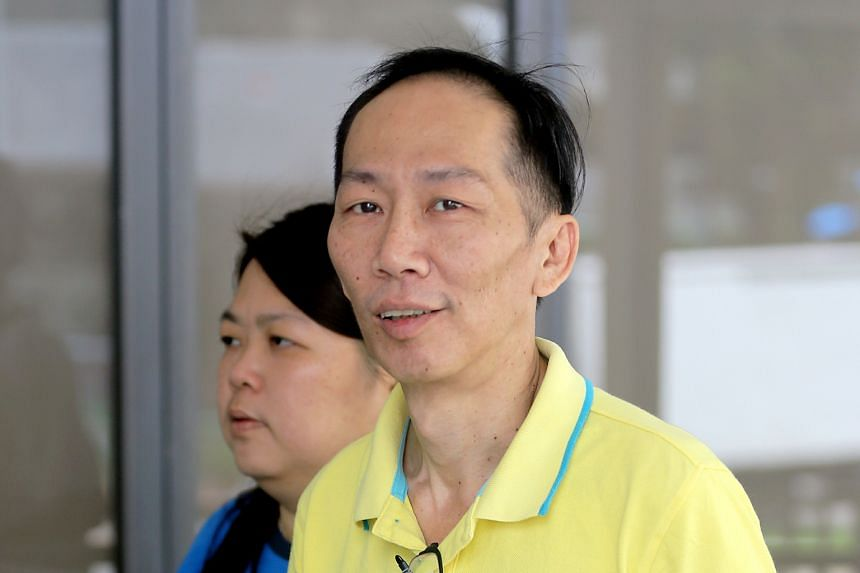 Chin Peng Sum arriving at the State Courts with his wife yesterday. Chin, who has been with the ICA since February 1998, has been suspended from service since June 2017.