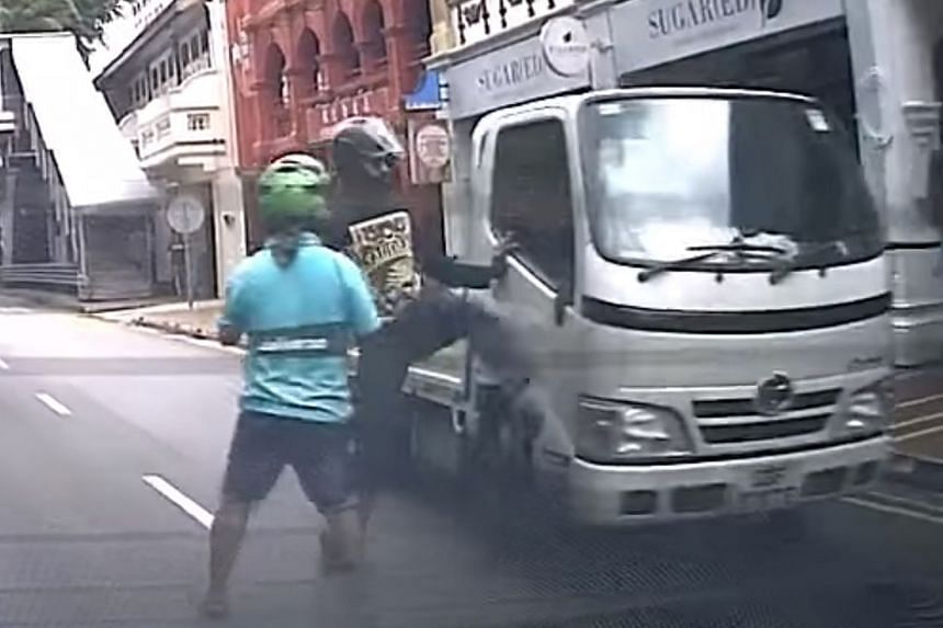 The video shows a motorcyclist in black kicking the lorry's side mirror, breaking it. The lorry then suddenly accelerates towards him, forcing him to run.