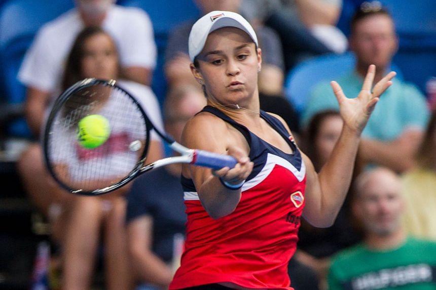Ashleigh Barty hits a return against Garbine Muguruza of Spain.