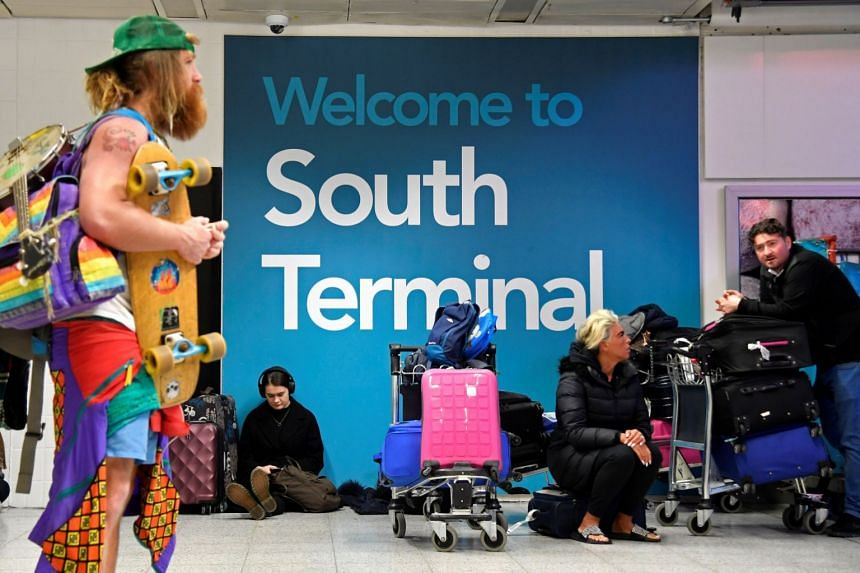 Passengers wait in the South Terminal building at Gatwick Airport after drone activity stopped flights.