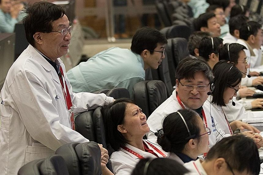Above: An image of the far side of the Moon taken by the Chang'e-4 probe. Left: Researchers at the Beijing Aerospace Flight Control Centre celebrating the landing yesterday.