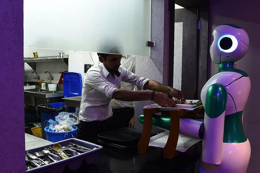 A Nepali-made robot waiter picking up food from the kitchen for customers at a Kathmandu restaurant. While technological advances in automation are starting to handle thousands of routine tasks and will eliminate many low-skill jobs, they are also cr
