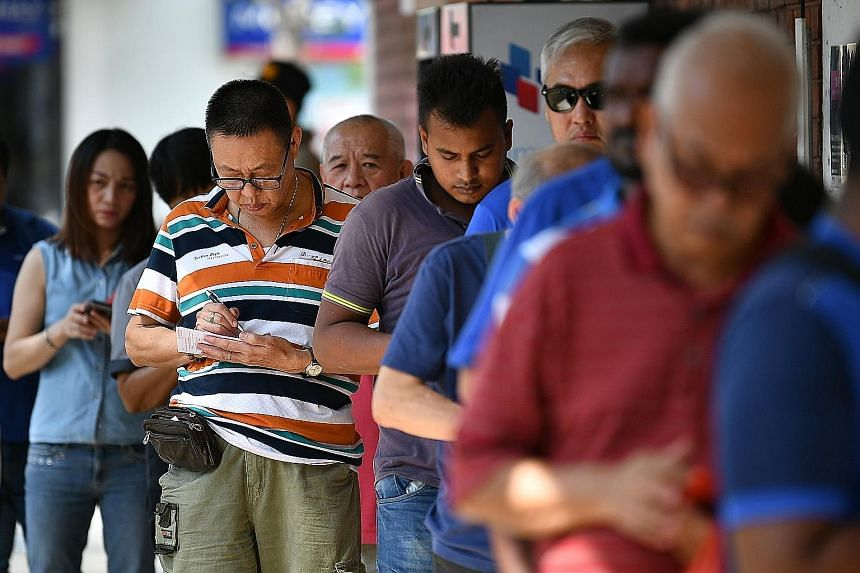 Punters queueing up to buy Toto tickets at the 7-Eleven outlet at Block 102 Yishun Avenue 5 yesterday. Last night, a single punter won the Group 1 cascade draw prize of $9,731,377. The winning ticket was sold at FairPrice Changi Business Park Hyperma