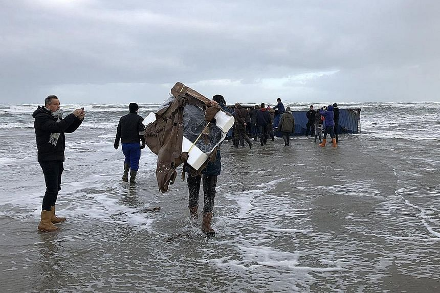 A treasure hunter (above) carrying what looks like a TV set still in its packaging from a beached container. The ship MSC ZOE (right) lost up to 270 containers in a North Sea storm.