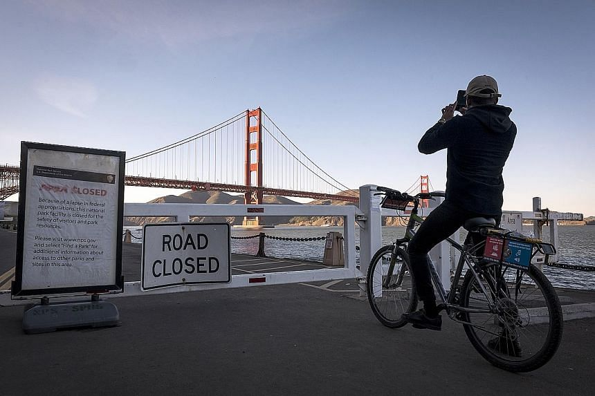A cyclist snapping a photo outside the closed entrance to Fort Point in the Golden Gate National Recreation Area in San Francisco, California, on Wednesday.
