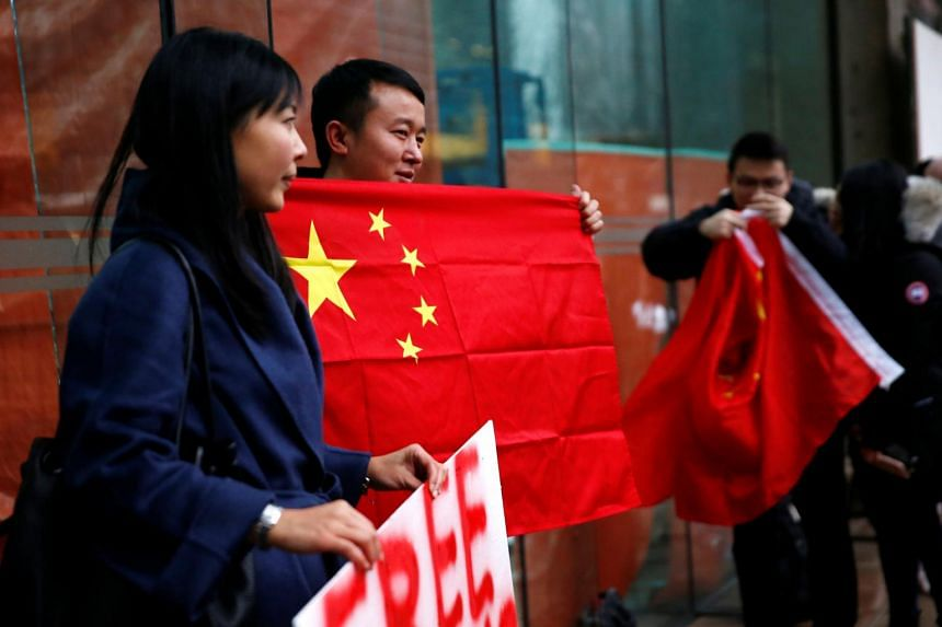 A man holds a Chinese flag outside the B.C. Supreme Court bail hearing of Huawei CFO Meng Wanzhou on Dec 11, 2018.