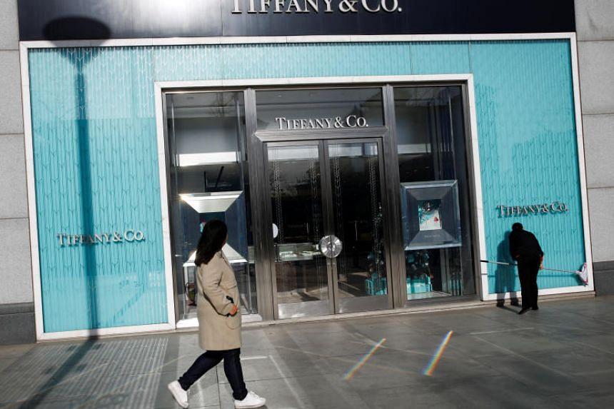 A woman walks past a Tiffany & Co store in a luxury shopping street in Beijing, Dec 4, 2018.