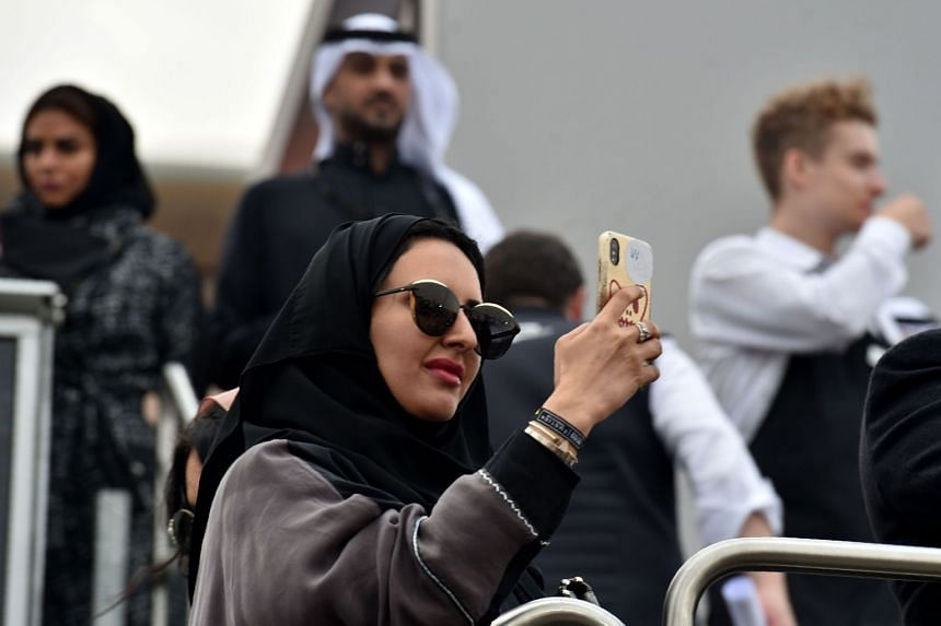 A Saudi woman takes photographs with her mobile phone in Riyadh.