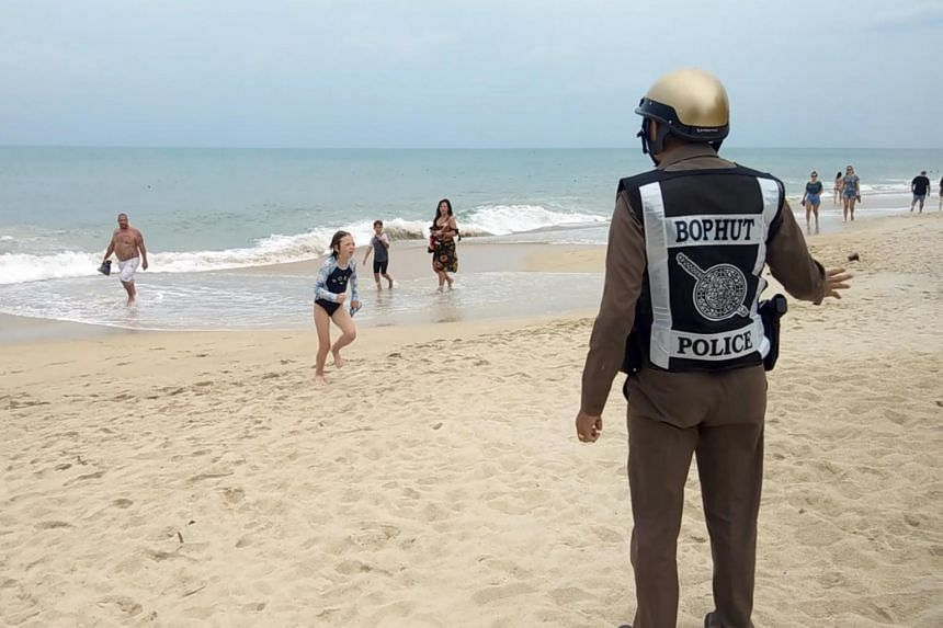 A Thai police officer warns tourists about a swimming ban due to a weather warning at a beach of Koh Samui Island, on Jan 3, 2019.
