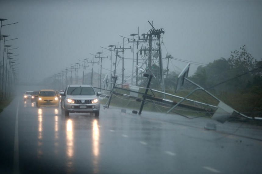 Cars and fallen electricity poles seen along a road as tropical storm Pabuk approaches the southern province of Nakhon Si Thammarat, Thailand, on Jan 4, 2019.