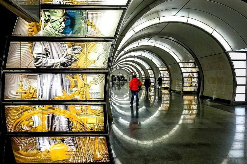 Cylindrical white light boxes (above) double as seats at the Solntsevo metro station; while artworks (left) dot the walls of the Fonvizinskaya station.