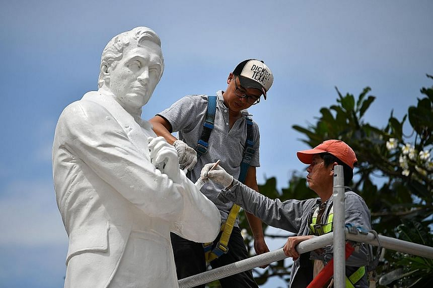 Above: A team from Hong Hai Environmental Art unwrapping the statue of Munshi Abdullah. The four new statues were officially unveiled yesterday. Left: Restoration work being done on the statue of Raffles.