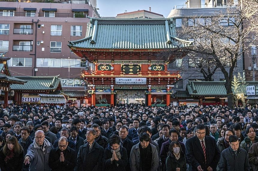 People offering prayers on the first business day of the year at the Kanda Myojin shrine in Tokyo, Japan, yesterday. Japan's benchmark bond yield fell to the lowest in more than two years as a stronger yen and a slowdown in global manufacturing spurr