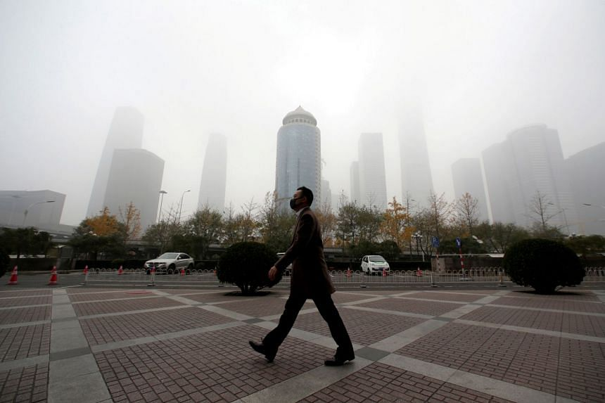 File photo of a man walking in the central business district on a polluted day after a yellow alert was issued for smog, in Beijing, China, on Nov 14, 2018.