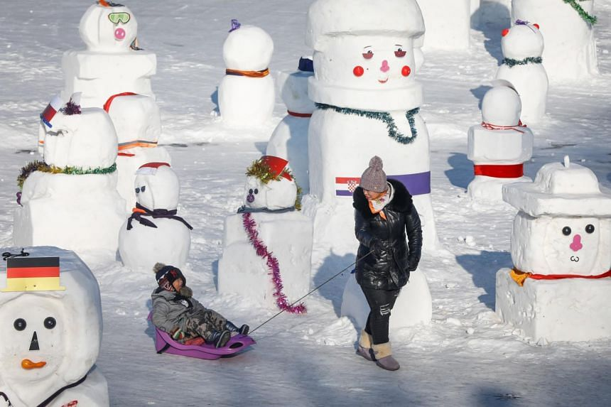 A woman walks with a child next to snowmen at the Songhua River at the festival in Harbin, in China's northern Heilongjiang province on Jan 5, 2019.