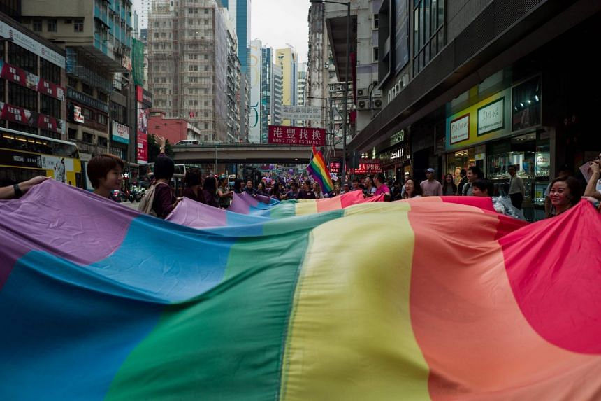 Participants holding a large rainbow flag as they take part in the annual pride parade at Victoria park in Hong Kong on Nov 17, 2018.