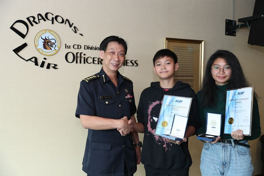 Colonel Lim Boon Hwee (left) presenting the awards to siblings Joshua Cordova (middle) and Mikkaela Cordova.