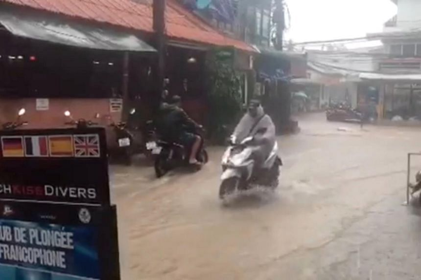 Motorcyclists ride along a flooded street as Tropical Storm Pabuk descends upon Koh Tao Island, Thailand, on Jan 5, 2019, in this still image taken from a video obtained from social media.