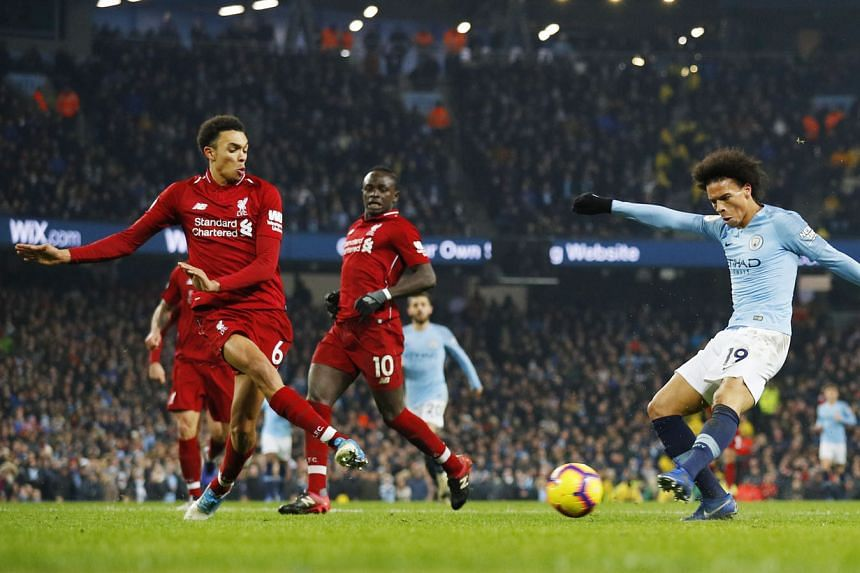 Above: Manchester City defender John Stones making a last-ditch tackle to keep the ball out of his goal by 1.12cm and away from Liverpool's Mohamed Salah. Far left: Salah grimacing after being felled by a tackle by City captain Vincent Kompany as a c