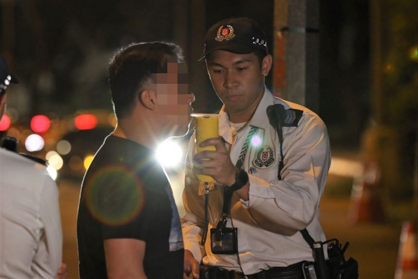 A policeman conducts a breathalyser test during anti-drink driving operations.