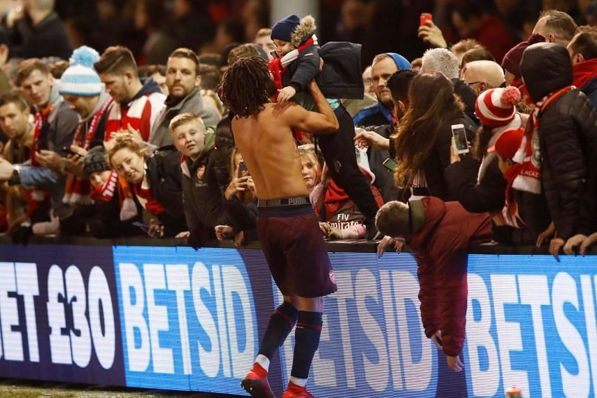 Arsenal's Mohamed Elneny celebrates after the match with fans.