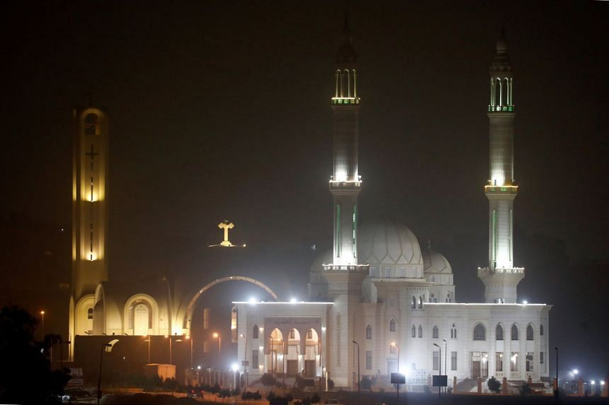 Minarets of a mosque and a cross on top of a church are seen during cold weather before Sunday's Coptic Christmas Eve Mass in Cairo.