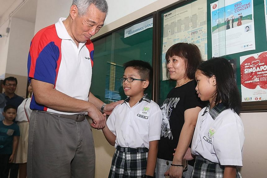 Prime Minister Lee Hsien Loong congratulating Edusave Award recipient Lim Zhe Wei from Teck Ghee Primary School, who is accompanied by his mother Feng Biao Mei and sister Lim Zhi Yi.