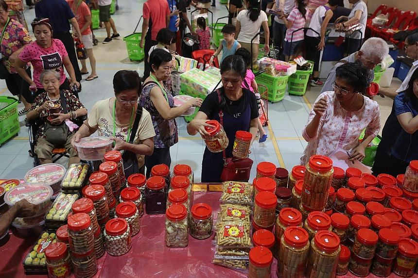 Shoppers choosing tidbits at Henderson Community Club yesterday, as they got to stock up early on groceries and goodies for the Chinese New Year. Volunteers turned an empty hall into a marketplace for 170 low-to middle-income families who may not qua