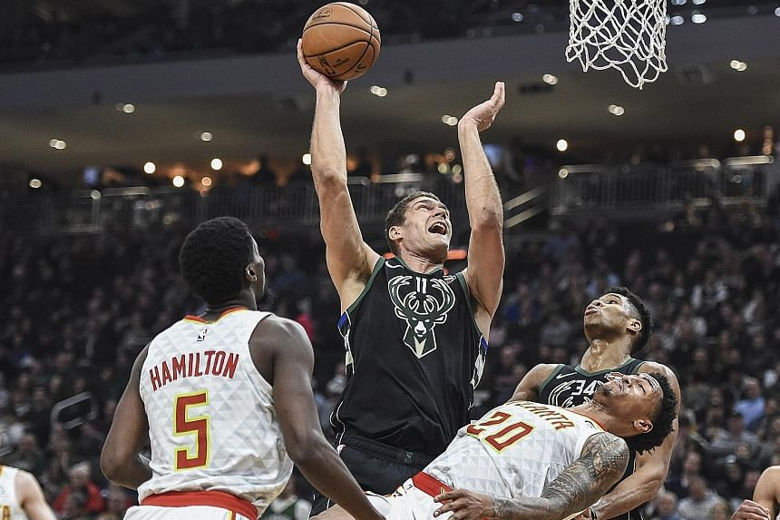 Bucks centre Brook Lopez taking a shot as Hawks guard Daniel Hamilton (left) and forward John Collins defend, while forward Giannis Antetokounmpo gives support. The Bucks won 144-112 at the Fiserv Forum in Milwaukee, Wisconsin on Friday night.