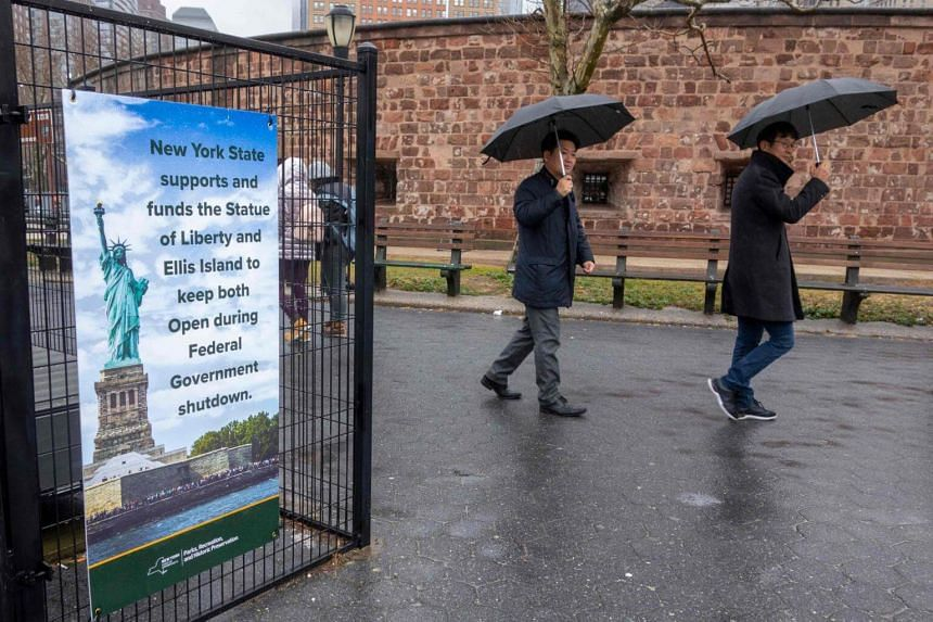People walking past a sign announcing that New York state is funding the Statue of Liberty and Ellis Island during the goverment shutdown, on Jan 5, 2019.