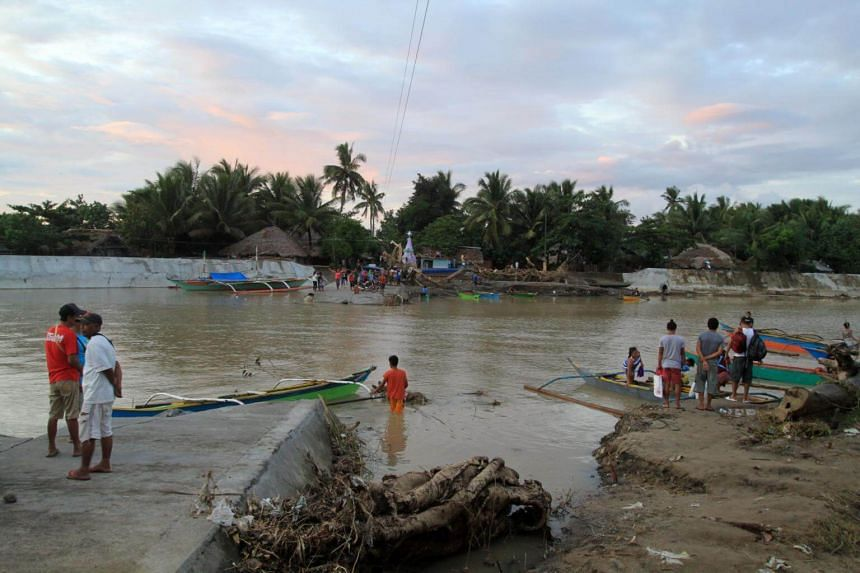 Villagers inspect a damaged road at a flooded community in the town of Bulan, Philippines, on Dec 31, 2018.