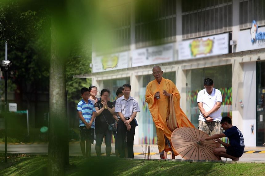 A priest performing rites near the Woodlands Close office unit where a boy fell eight storeys to his death after attempting to escape from the window, on Jan 6, 2019.