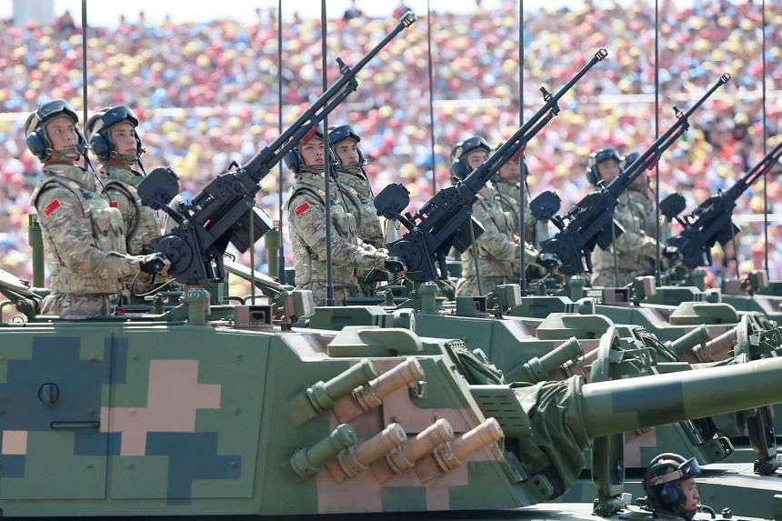 Chinese soldiers on armoured assault vehicles during a military parade in Beijing. President Xi Jinping has once again said that China reserves the right to use force to achieve reunification with Taiwan, even as it strives to achieve this goal via p