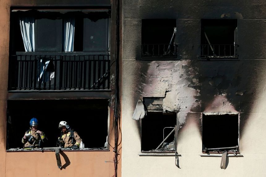 Firefighters check the damage after extinguishing a fire that broke out at an apartment building in Badalona.