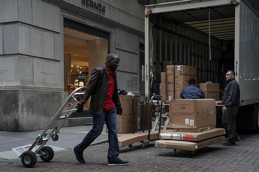 Workers unloading a truck in New York City. The US economy added 312,000 jobs last month, suggesting continued strength in the economy. The attention this week will be on whether talks in Beijing lead to progress in US-China trade relations.