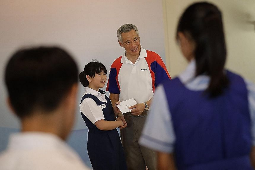 Townsville Primary School pupil Chloe Wee Xin Lei receiving her awards from Prime Minister Lee Hsien Loong yesterday.