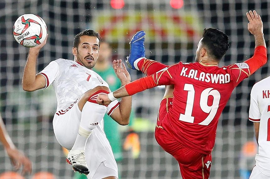 The UAE's Ali Mabkhout (far left) challenging Bahrain's Kamail Al Aswad for the ball during the teams' 1-1 draw in the Asian Cup Group A match on Saturday.