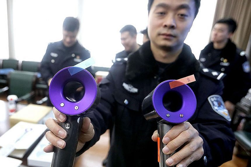 A Shanghai police officer showing a fake (left) and real Dyson hairdryer last Friday.