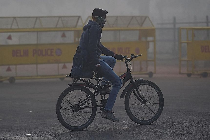 A cyclist making his way in the smog in New Delhi last Thursday. Air quality was very poor despite a respite yesterday.