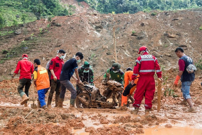 Rescue workers salvage a buried motorcycle after landslides hit Sirnaresmi village at Cisolok district in Sukabumi, West Java province, Indonesia, on Jan 2, 2019.
